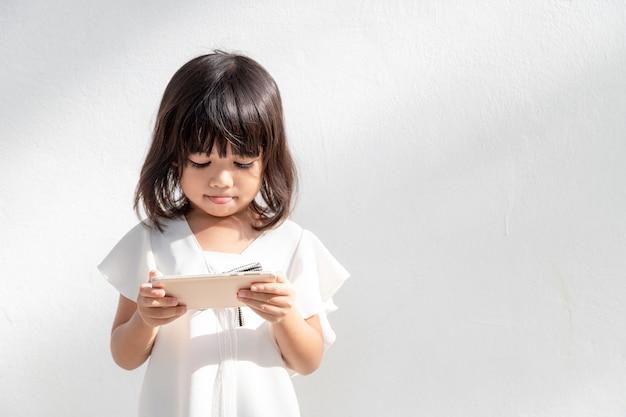 Маленькая девочка сосредоточена на телефоне, посмотрите на концепцию технологии смартфона для детей