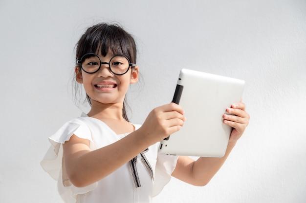 小さな女の子は子供のためのスマートフォン技術の概念を見て電話に集中しています
