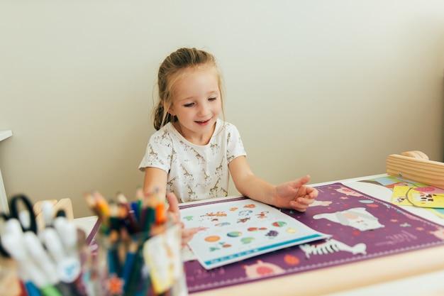 어린 소녀는 그의 책상에 앉아있는 동안 배우게되어 기쁘다. 홈 스쿨 개념입니다. 교육 개념. 아이 학습 배경. 유아 수제 게임. 유치원 교육.