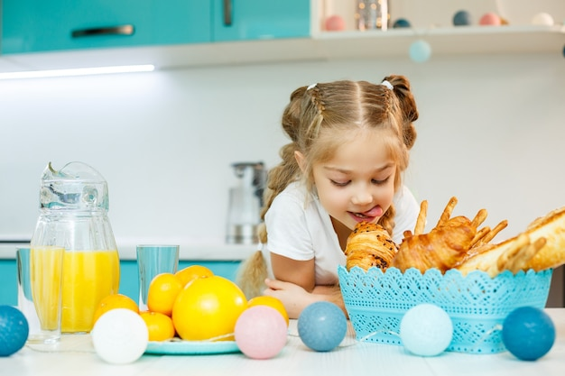 小さな女の子がクロワッサンとオレンジジュースを使ってキッチンで朝食をとっています。