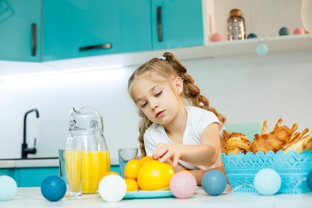 어린 소녀가 크루아상과 오렌지 주스로 주방에서 아침 식사를 하고 있습니다.