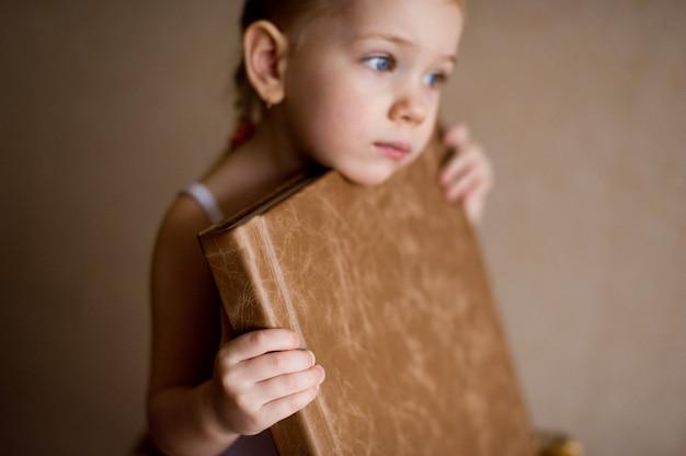 Маленькая девочка держит фотоальбом в натуральной коричневой коже.