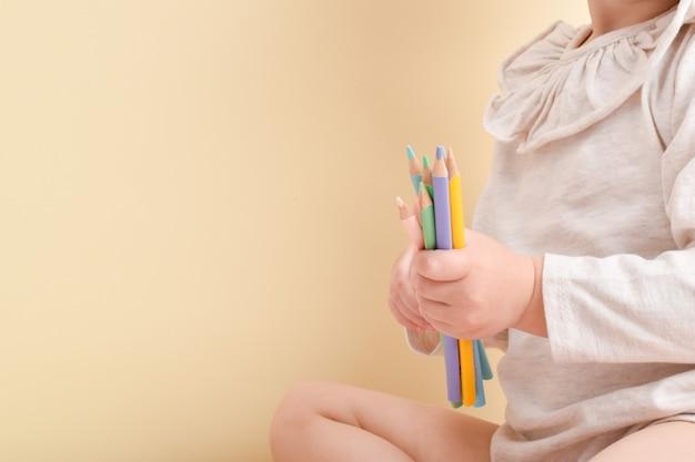 小さな女の子が鉛筆を手に持っています。クリエイティブクラス。子供のための絵。
