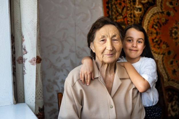 小さな女の子が曽祖母と一緒に笑っています
