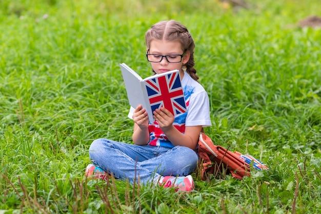 어린 소녀가 잔디밭에 앉아 영어를 배우고 있습니다.
