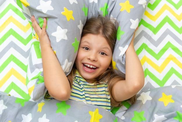 小さな女の子がベッドに横たわっていて、枕で耳を覆っています。