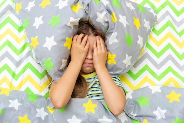 어린 소녀는 침대에 누워 있고 장난꾸러기이고 울고 일어나기 싫고 학교에 가고 싶지 않습니다.