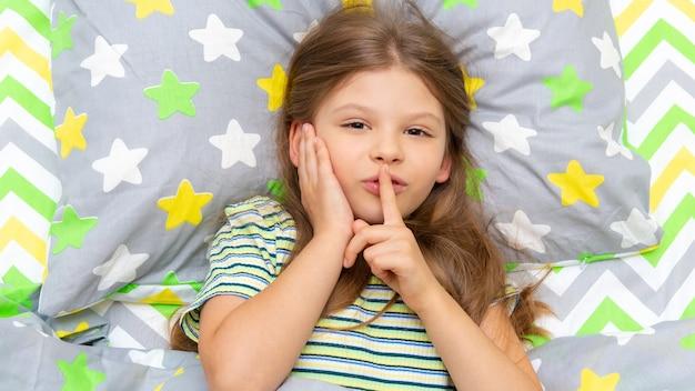 小さな女の子がベッドに横になっていて、驚いて指を指しています。静かに。その少女は眠りたい。