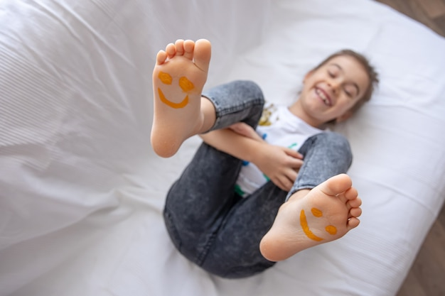 Маленькая девочка лежит на диване с раскрашенными красками ступнями.