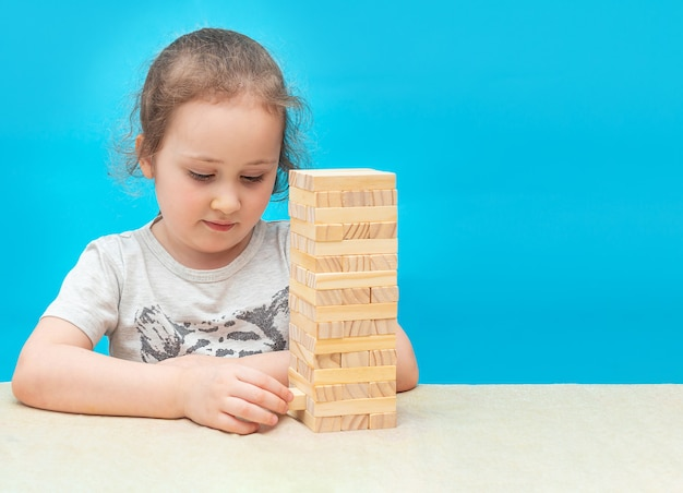 Маленькая девочка играет в настольную игру из деревянных блоков