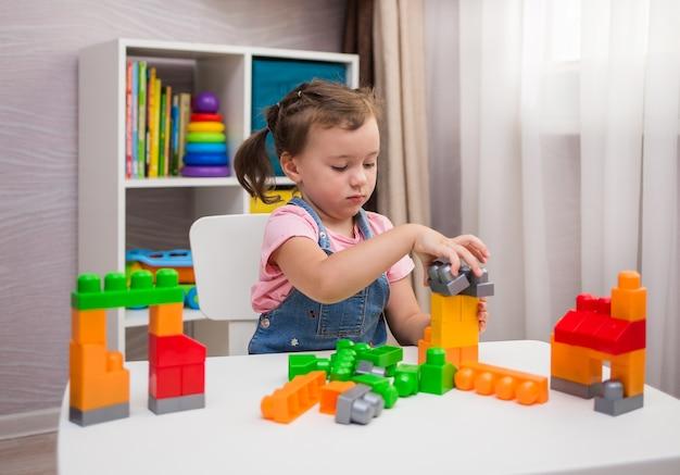 小さな女の子が子供部屋のテーブルでマルチカラーのコンストラクタを遊んでいます
