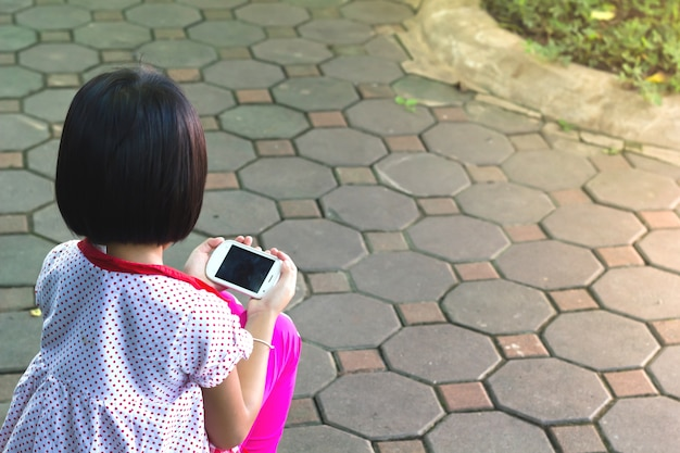 小さな女の子が彼女のスマートフォンでゲームをしています。彼女に焦点を合わせました