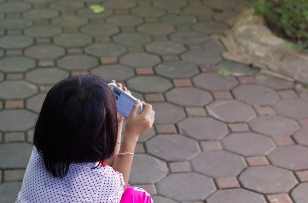 小さな女の子が彼女のスマートフォンでゲームをしています。彼女の体に焦点を当てました。