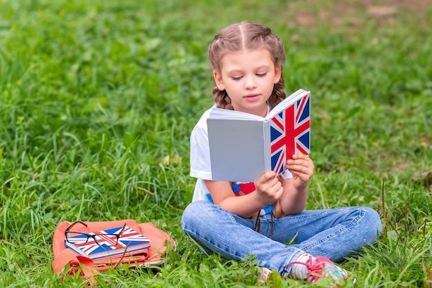 어린 소녀가 잔디밭에 앉아 영어로 된 책을 읽고 있습니다.