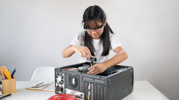 Маленькая девочка ремонтирует компьютерную технику за белым рабочим столом.