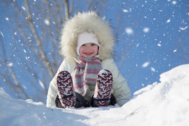 小さな女の子が雪をかぶった丘に乗っています