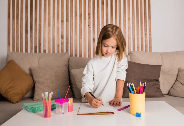 어린 소녀가 테이블에 앉아 앨범에 펠트 펜으로 그림을 그리고 있습니다