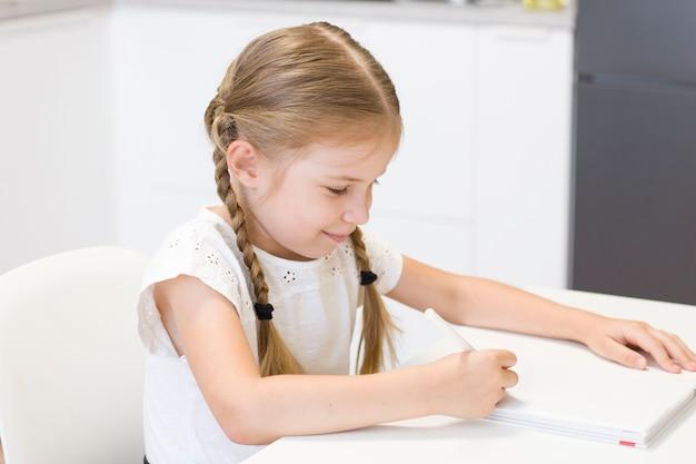 어린 소녀가 테이블에 앉아 그림을 그리고 있습니다. 학생. 학교. 9월 1일