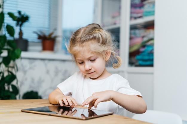 小さな女の子がタブレットを持ってテーブルに座って、手を上げて笑顔で幸せになり、幸せを体験しています。高品質の写真