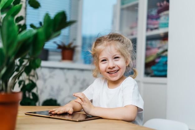 어린 소녀가 태블릿을 들고 탁자에 앉아 손을 공중에 들고 웃고 행복하며 행복을 경험하고있다.