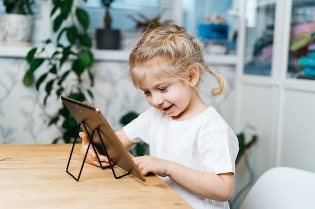 어린 소녀가 태블릿 테이블에 앉아 있습니다.
