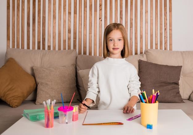 Маленькая девочка сидит за столом с художественными принадлежностями в комнате
