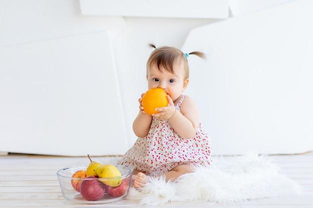 Маленькая девочка сидит в светлой комнате с тарелкой фруктов и ест апельсин