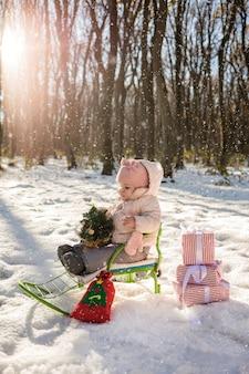 Маленькая девочка сидит в санях с маленькой елкой и подарками в виде зимнего леса и снега.