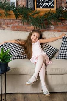 小さな女の子が市松模様の枕と居心地の良いソファに座っています。