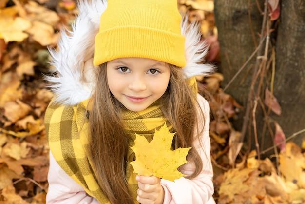 小さな女の子が秋の落ち葉に座っています。
