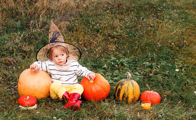 어린 소녀가 큰 마법사 모자, 빨간 부츠를 신고 풀밭에 앉아 있고, 크고 작은