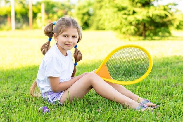 Маленькая девочка сидит на траве с теннисной ракеткой в руках.