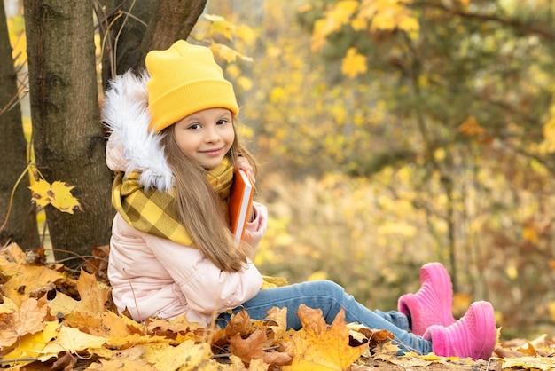 小さな女の子が秋の森の地面に座っています。
