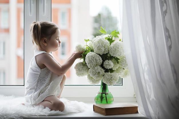 小さな女の子が窓辺に座っています。窓際の花瓶に花束と花を嗅ぐ少女。窓際に白い花の花束と白いドレスを着た小さな王女。