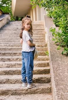 小さな女の子が公園に立って、帽子を手に持っています。子供は気分を害し、動揺します。