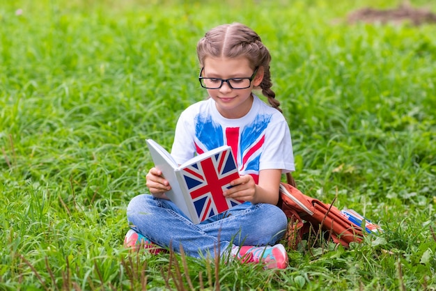 어린 소녀가 잔디밭에 앉아 영어 책을 공부하고 있습니다.