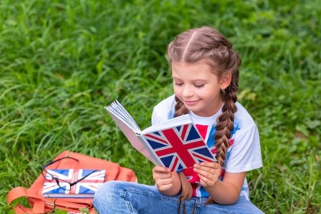 Маленькая девочка изучает книгу по английскому языку, сидя на лужайке.