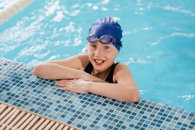 Маленькая девочка плавает и улыбается в бассейне. здоровый образ жизни.