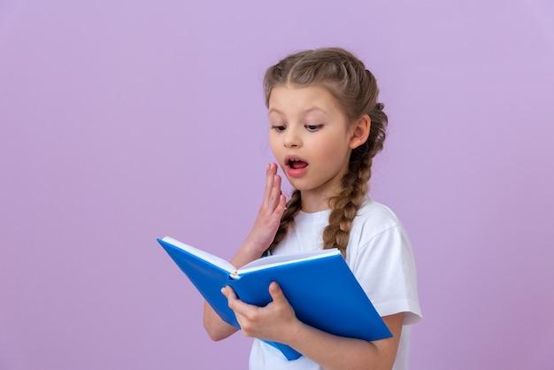 어린 소녀는 흥미로운 책을 읽고 매우 놀랐습니다.