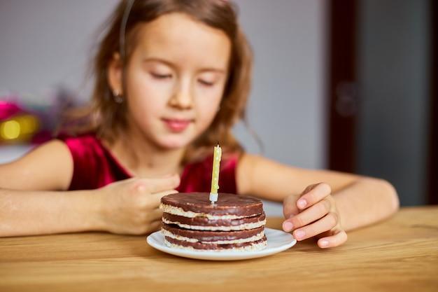 Маленькая девочка в шляпе на день рождения смотрит на именинный торт