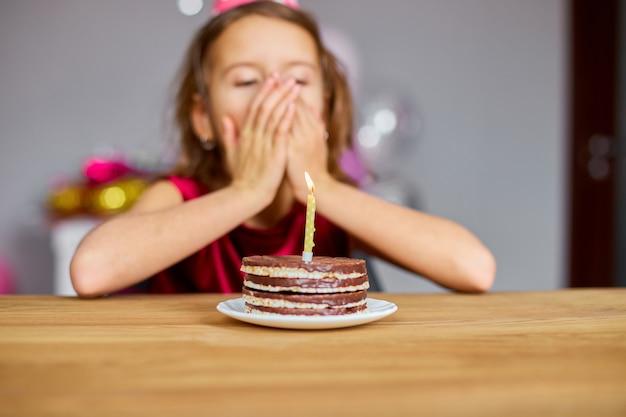 생일 모자를 쓰고있는 어린 소녀가 생일 케이크를보고 소원을 빌며