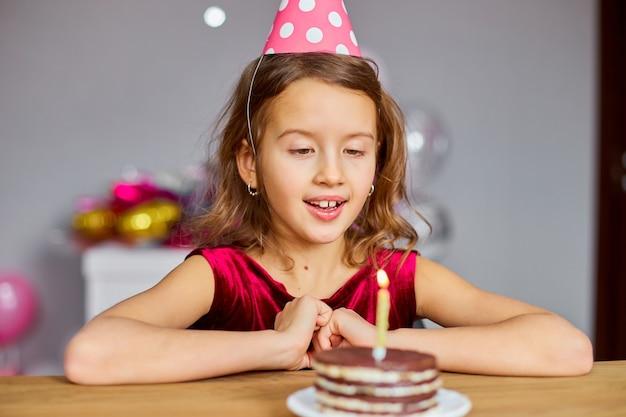 Маленькая девочка в шляпе на день рождения загадывает желание, глядя на именинный торт