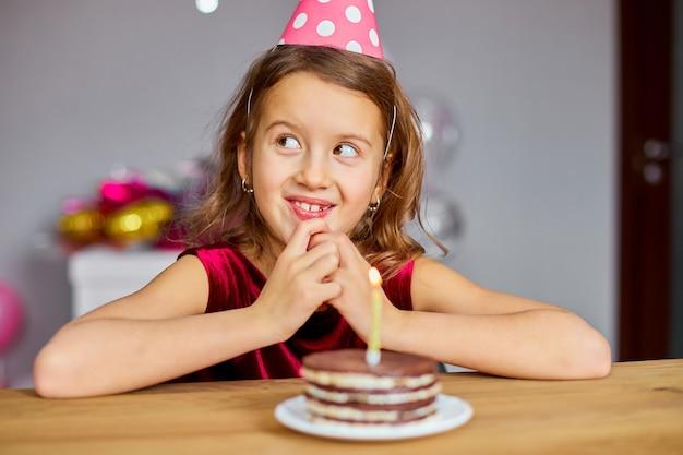 생일 모자를 쓰고있는 어린 소녀가 소원을 빌며