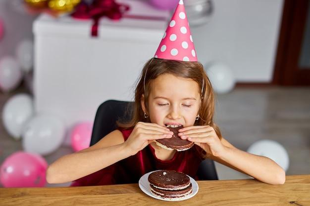 Маленькая девочка носит вкусный день рождения, съесть торт ко дню рождения для концепции празднования вечеринки.
