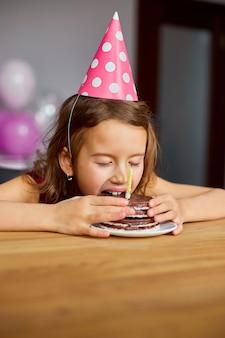 어린 소녀가 맛있는 생일을 입고 생일 케이크를 먹습니다.