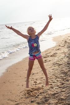 Маленькая девочка вскочила на песчаный берег моря. счастливые летние каникулы. размытое движение.