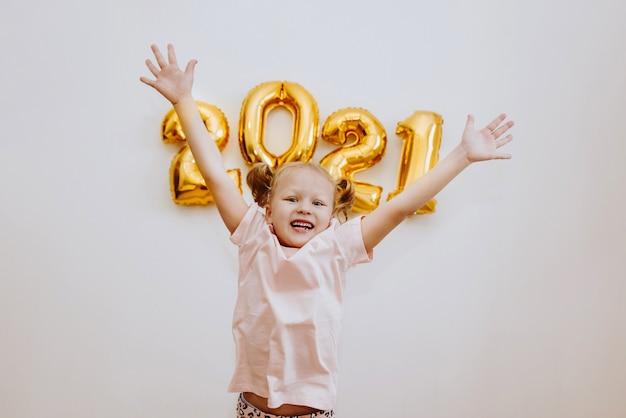 어린 소녀가 2021 년 크리스마스와 새해를 축하하며 황금 숫자를 배경으로 점프하고 기뻐합니다.
