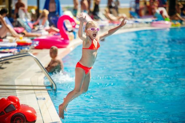어린 소녀가 여름 방학 동안 워터 파크의 수영장으로 뛰어 들어갑니다.