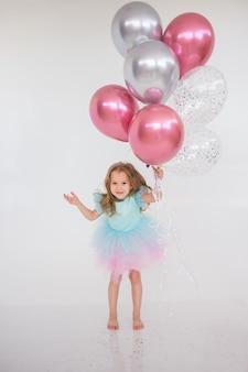 어린 소녀는 텍스트를 위한 장소가 있는 흰색 배경에 풍선 다발을 가지고 점프합니다. 휴일 생일