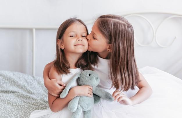 小さな女の子が妹の頬にキスをします。子供の寝室で休んでいる女の子